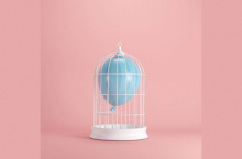 A pale blue balloon in a white birdcage against a pink background
